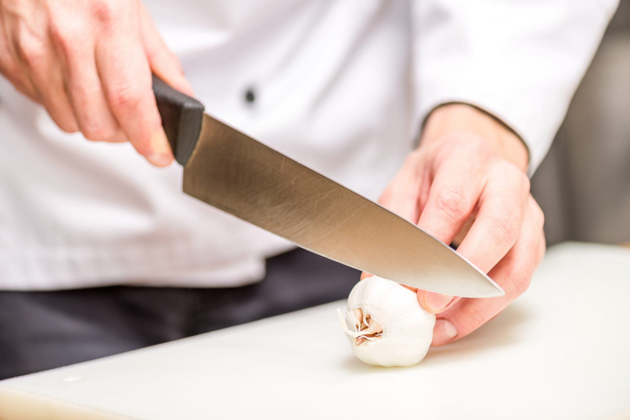 man chopping garlic bulb with knife